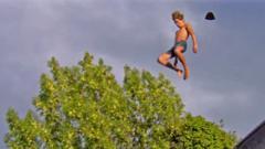 A man flies through the air as his hat blows of his head