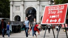 People walking past Covid-19 warning sign in Marble Arch, London