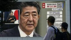 People watch a broadcast of Shinzo Abe's resignation announcement in Tokyo, Japan (28 August 2020)
