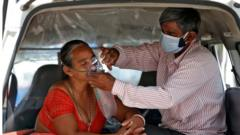 """The husband of Nanduba Chavda adjusts his wife""""s oxygen mask as they wait in a car to enter a COVID-19 hospital for treatment, amidst the spread of the coronavirus disease (COVID-19) in Ahmedabad, India, April 28, 2021."""
