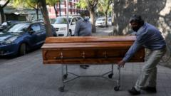 Funeral home workers move a casket outside a morgue at a hospital area, during the coronavirus disease (COVID-19) pandemic, in Santiago, Chile April 8, 2021