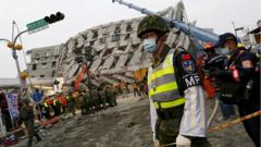 A soldier stands guard in front of a collapsed building after an earthquake hit Tainan, southern Taiwan
