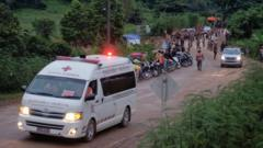 An ambulance carries one of the rescued boys to hospital as people look on