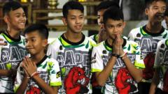 Some of the 12 members of the Wild Boar soccer team, who were rescued from the Tham Luang cave, greet the media