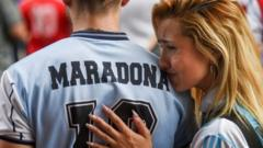 A woman rests on the shoulder of a man wearing a Maradona football shirt