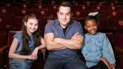 three-actors-from-frozen-the-musical-sit-in-theatre-seats