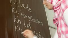 Girl in a headscarf writing in German on a blackboard