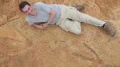 Dr Fabien Knoll lies next to the massive footprints