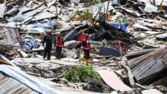 Rescuers walk past debris at Perumnas Balaroa village in Palu, Indonesia's Central Sulawesi on October 5, 2018, following the September 28 earthquake and tsunami.