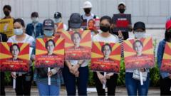 Protesters wearing face masks hold placards with the portraits of Aung San Suu Kyi during the demonstration.