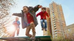 Children-jumping-in-front-of-tower-block.