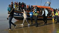 Migrants with children are escorted after being picked up by a lifeboat while crossing the English channel at a beach in Dungeness, southeast England.