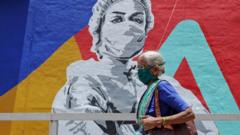 An elderly woman wearing a mask walks past a mural on Covid-19 in Mumbai.