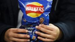 A boy holds a Walkers crisp packet in his hands