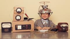 A boy wears a colander on his head and sits next to cardboard boxes connected with string to look like a home made brain scanner.