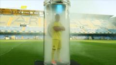 A football player in a glass tube full of smoke on a pitch