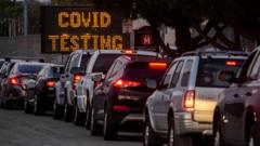 A long line of vehicles line up to take Covid-19 tests at dusk at Long Beach City College-Veterans Memorial Stadium in December