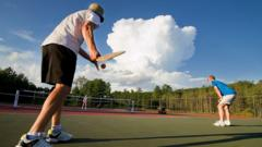 A pickleball player gets ready to serve