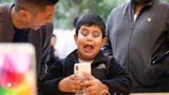 A boy pulls a face at a mobile phone