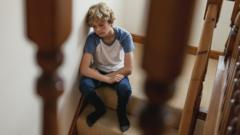 Boy looking sad while sitting on stairs