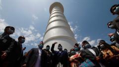 Nepal's Prime Minister KP Oli (C) waves during the inauguration of Dharahara tower, Kathmandu, 24 April
