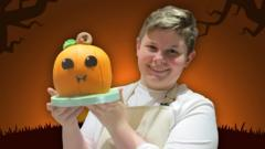 Junior Bake Off winner Fin holding his pumpkin cake.