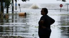 A woman stands in front of a flooded road near Lake Pontchartrain as hurricane Barry approaches in Mandeville, Louisiana
