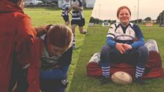 A young rugby player called Alex sitting down ready to be interviewed.
