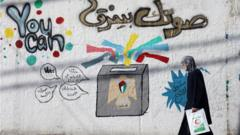 Woman walks past election campaign mural in Gaza City (01/04/21)
