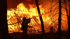 A fire fighter tackles the wildfire burning a home in Magalia, California