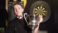 Darts player Leighton with his trophy.