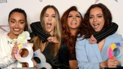 Little Mix pulling silly faces at a ceremony with awards