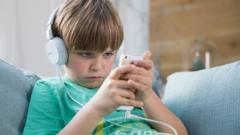 A boy with headphones on looks at his mobile phone