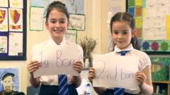 Two girls hold signs saying 1st born and 2nd born