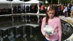 A-relative-lays-a-wreath-as-a-remembrance-service-takes-place-for-the-victims-of-the-Omagh-bombing-on-it's-20th-anniversary-on-August-12-2018