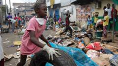 Girl in Sierra Leone taking part in national cleaning day