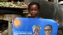 A child holds a campaign poster with photographs of incumbent Benin President Patrice Talon (R on poster) and running mate Mariam Talata (L on poster) at the market in Cotonou on April 8, 2021.