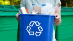 Person holding a plastic recycling bin