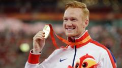 Long jump gold medallist Britain's Greg Rutherford holds up his medal during the medal ceremony at the World Athletics Championships at the Bird's Nest stadium in Beijing