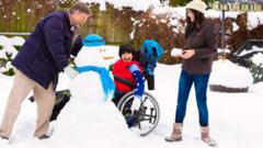 Family playing in snow with snowman