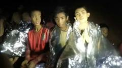 A video grab handout made available by the Thai Navy SEALs shows some of the members of a soccer team in a section of Tham Luang cave in Khun Nam Nang Non Forest Park