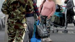 Members of the defence forces direct passengers arriving at Dublin Airport from one of 33 high-risk countries who will be transported to a mandatory 12-day hotel quarantine on Friday 26 March