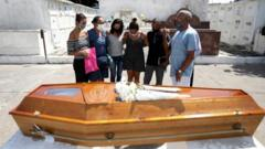 Relatives of Luiz Alves, 63, who died from coronavirus disease (COVID-19), stand by his coffin during the funeral at Inhauma cemetery in Rio de Janeiro, Brazil March 10, 2021