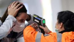 Woman's temperature being tested at an airport in Hong Kong