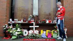 A Liverpool fan looks at tributes at the Hillsborough memorial at Liverpool's Anfield stadium.