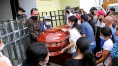 Family members bid farewell to one of the victims of the murder of eight people in Samaniego, Colombia, 16 August 2020.
