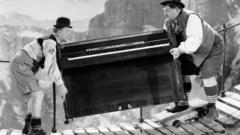 Oliver Hardy and Stan Laurel carry a piano over a bridge