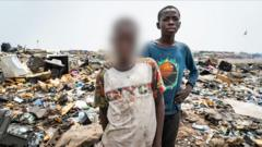 Malik, on the right, as a 'burner boy' on the Agbogbloshie dump in Accra, Ghana