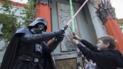 A boy battles Darth Vader with lightsabers