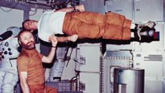 Jerry Carr demonstrates weightlessness by pretending to hold up Ed Gibson with one finger